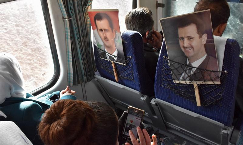لافتات تحمل صورة بشار الأسد في إحدى الحافلات في سوريا_كانون الأول 2016_(AFP)