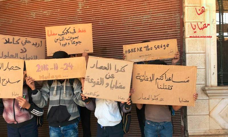 تعبيرية:أطفال بلدة مضايا في ريف دمشق يحملون مناشداتهم في لافتات - 24 تشرين الأول 2016 (صفحة هنا مضايا في فيس بوك)
