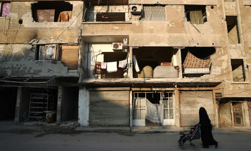 امرأة مع طفلها في مدينة دوما بالغوطة الشرقية_4 شباط_(AFP)