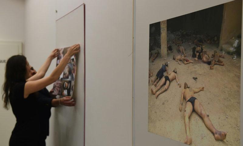 أعضاء في المنظمة السورية لضحايا الحرب يعلقون صورًا توثيقية لتعذيب السوريين داخل ومعتقلات النظام السوري، خلال معرض في جنيف في 17 اذار 2016 (AFP)