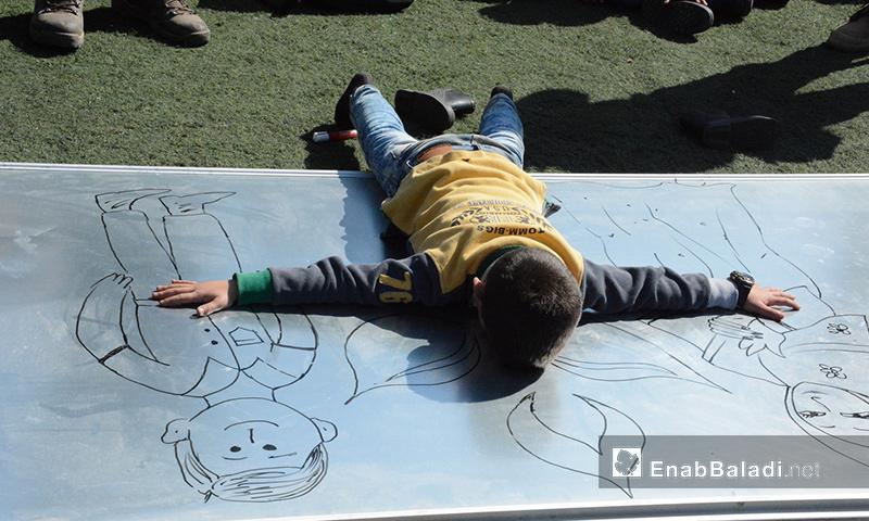 الطفل قاسم يحتضن رسمة خلال حفل داخل مخيم عطاء في إدلب - 23 شباط 2017 (عنب بلدي)