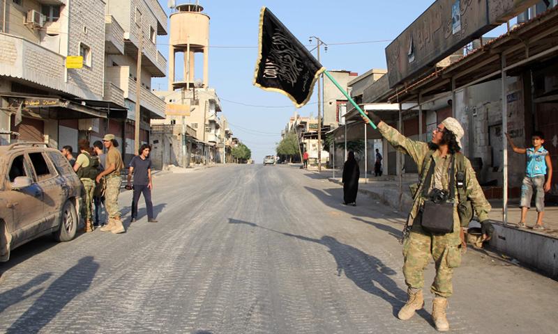 """مقاتل من """"لواء الأقصى"""" يرفع علم اللواء في مناطق سيطرته (إنترنت)"""