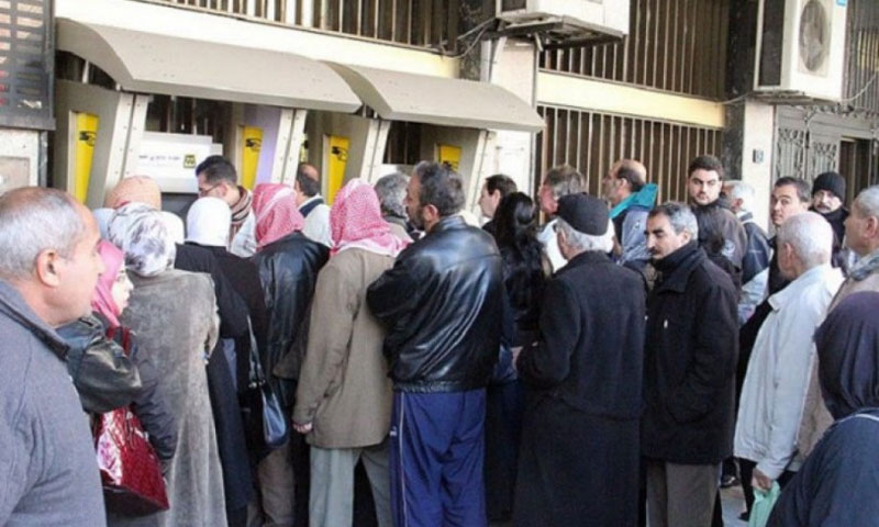 تجمع المتقاعدين أمام أحد الصرافات في سوريا لقبض رواتبهم (انترنت)