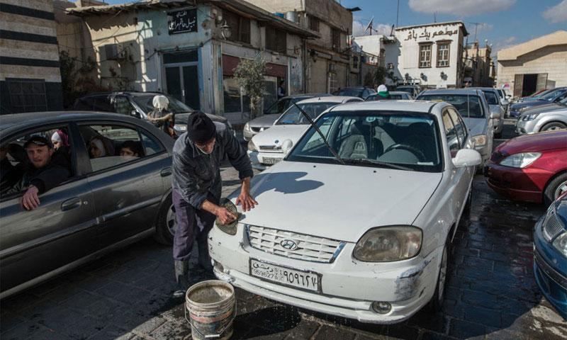 أحد سكان مدينة دمشق يقوم بتنظيف سيارته كانون الأول 2016(سبوتنيك)