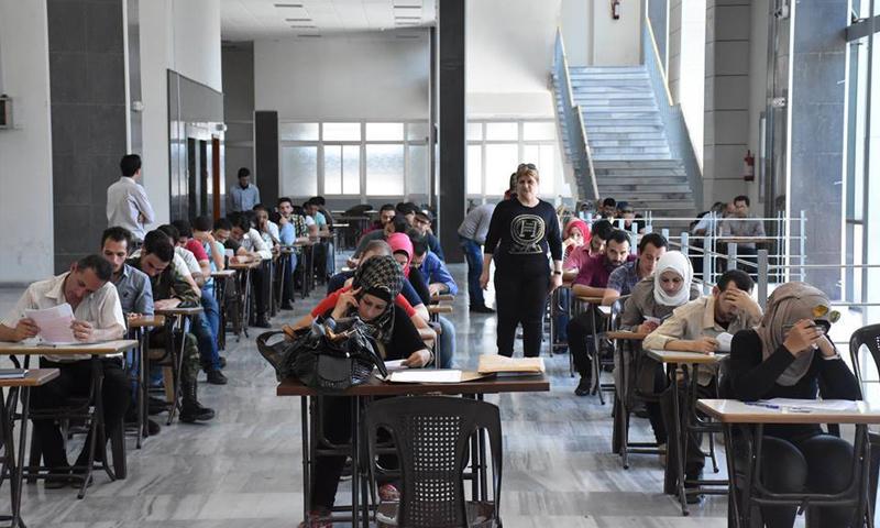 ازدحام في امتحانات جامعة دمشق ما اضطر الطلاب للتقديم في الممرات (إنترنت)
