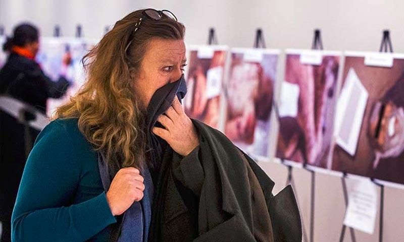تعبيرية: امرأة تنظر بأسى إلى صور السوريين في معرض قيصر لضحايا التعذيب داخل مقر الأمم المتحدة- أيلول 2015 (إنترنت)