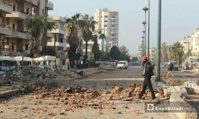 رجل يمشي قرب مكان سقوط قذيفة داخل حي الوعر في حمص- 11 شباط 2017 (عنب بلدي)