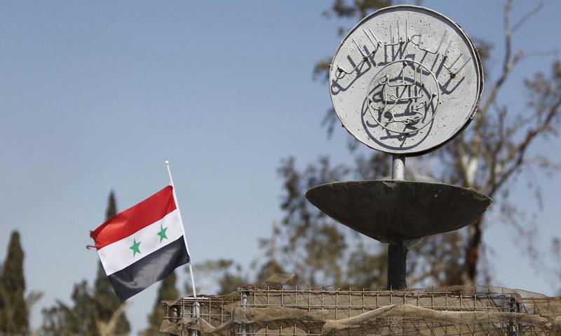 """علم النظام السوري إلى جانب شعار لتنظيم """"الدولة الإسلامية"""" في تدمر - 20 شباط 2017 (رويترز)"""