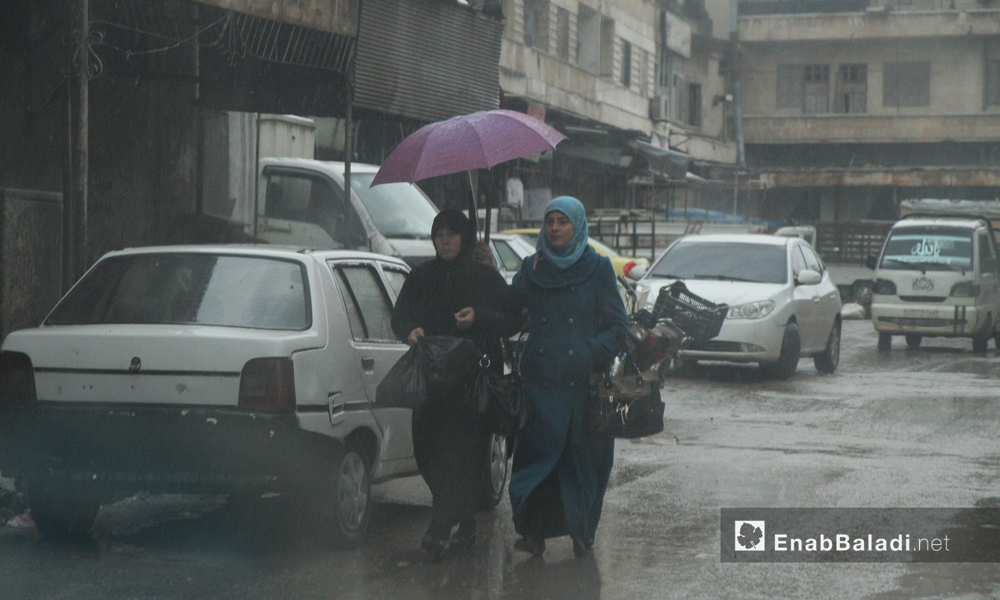 من سكان مدينة إدلب إثناء تساقط الأمطار - 11 آذار 2017 (عنب بلدي)