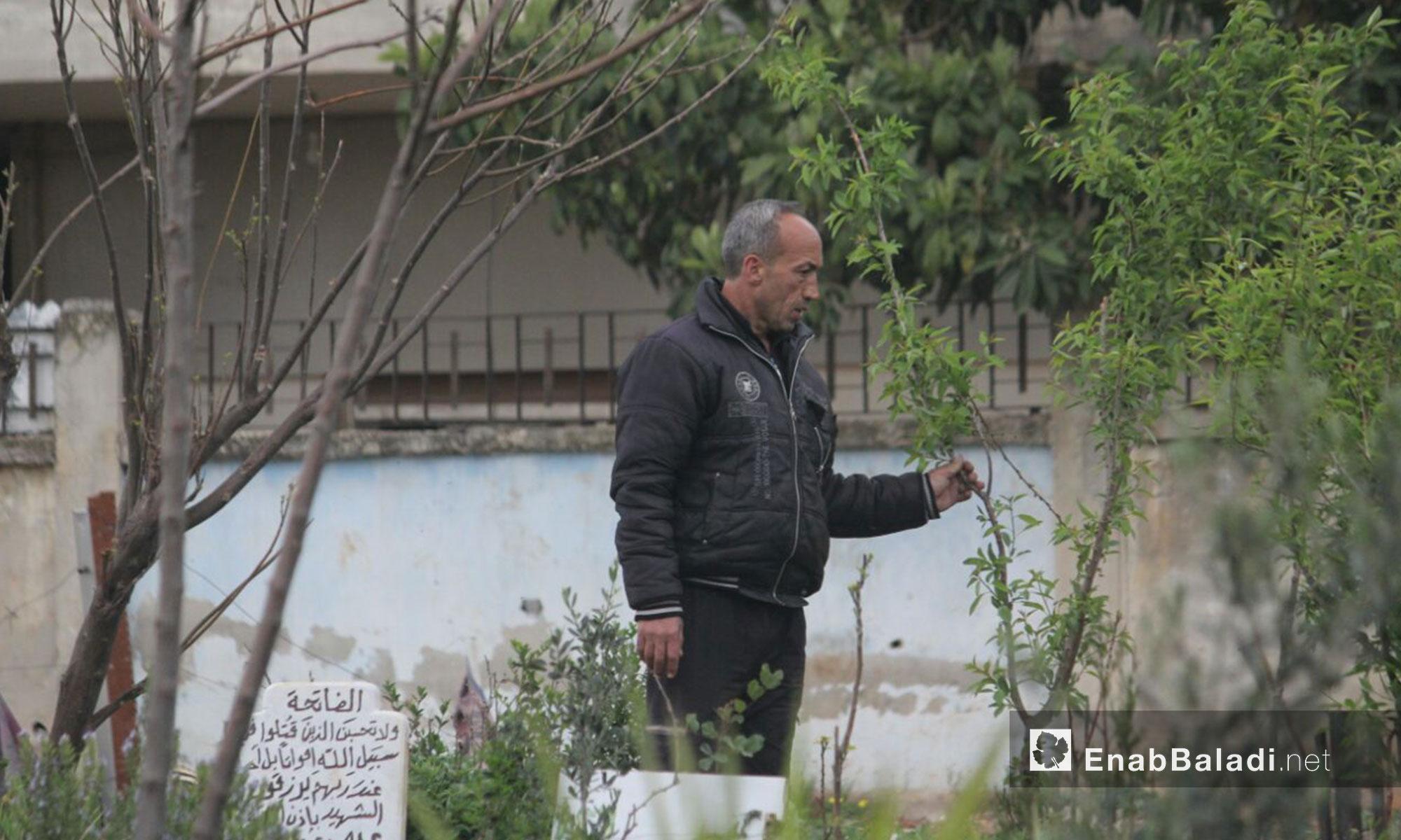 أحد المدنيين في حي الوعر يزور المقبرة مع دخول فصل الربيع - 30 آذار 2017 (عنب بلدي)
