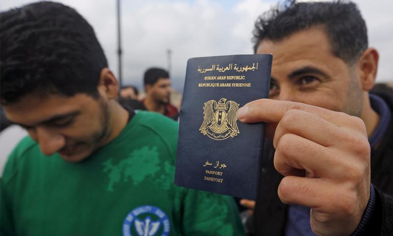 """لاجئ يحمل الجواز السوري بعد عملية إنقاذ في مدينة """"كوس"""" اليونانية - 29 أيار 2015 (رويترز)"""