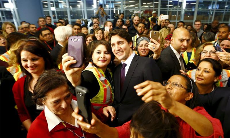 لاجئون سوريون يلتقطون الصور مع رئيس الوزراء الكندي جاستن ترودو - (انترنت)