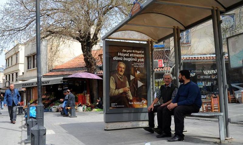 السوري علي حنكي في محطة حافلات عليها لافتة إعلانية تظهر صورته (الأناضول)