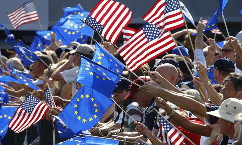 متظاهرون يحملون علم الولايات المتحدة وعلم الاتحاد الأوروبي (إنترنت)