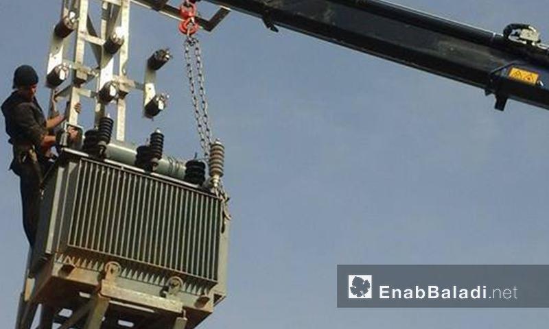 أرشيفية- عامل صيانة يحاول الوصول إلى محول كهربائي على أحد الأبرج في محافظة حلب (عنب بلدي)