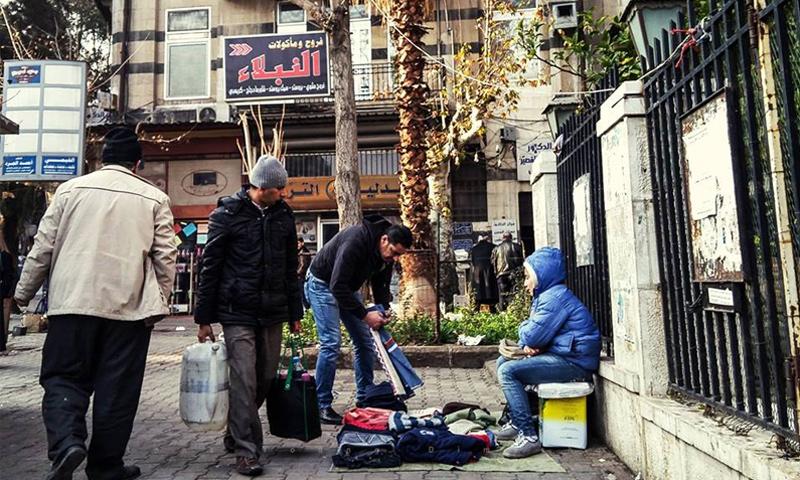 طفل سوري يبيع الملابس في الجسر الأبيض في دمشق (عدسة شاب دمشقي)