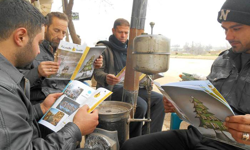 أسخاص يتصفحون مجلة طلعنا عالحرية (المجلة فيس بوك)