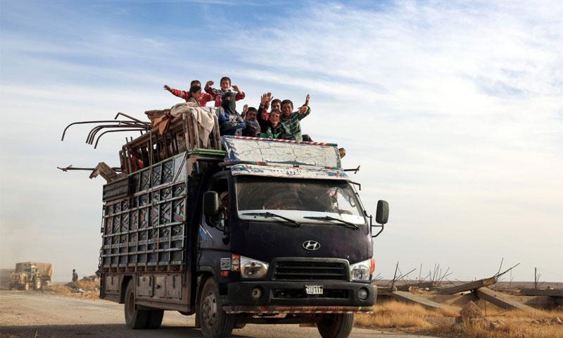 أطفال سوريين يعتلون شاحنة أثناء خروجهم من مدينة الرقة - أيلول 2016 -(AFP)