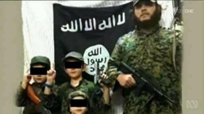 """خالد شروف وأطفاله قرب راية تنظيم """"الدولة الإسلامية"""" في سوريا (إنترنت)"""