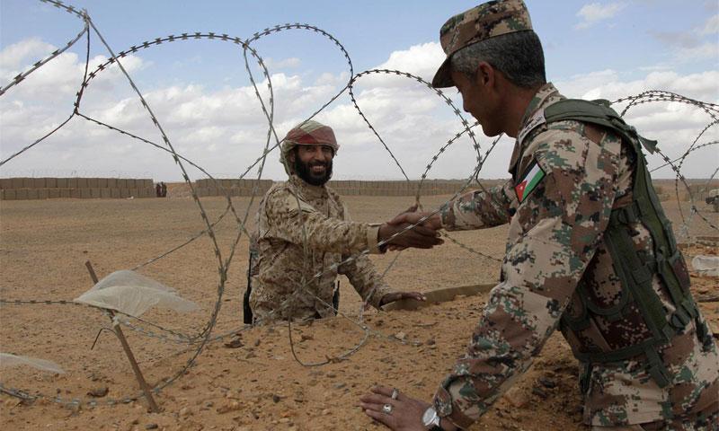 """مقاتل سوري من """"جيش العشائر"""" يصافح جنديًا أردنيًا على الشريط الحدودي عند مخيم الركبان - 14 شباط 2017 (AP)"""