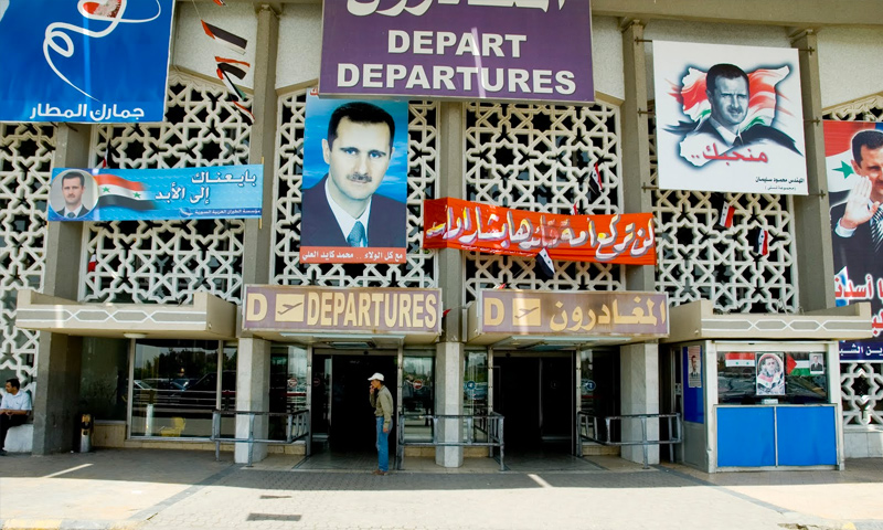 لافتات تدعم رئيس النظام السوري بشار الأسد في مطار دمشق (إنترنت)