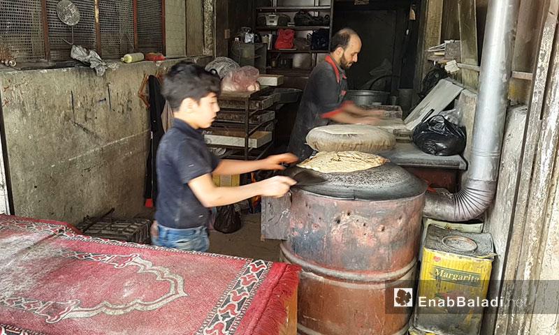 طفل يساعد أباه بالخبز على الصاج في الغوطة الشرقية - نيسان 2017 (عنب بلدي)