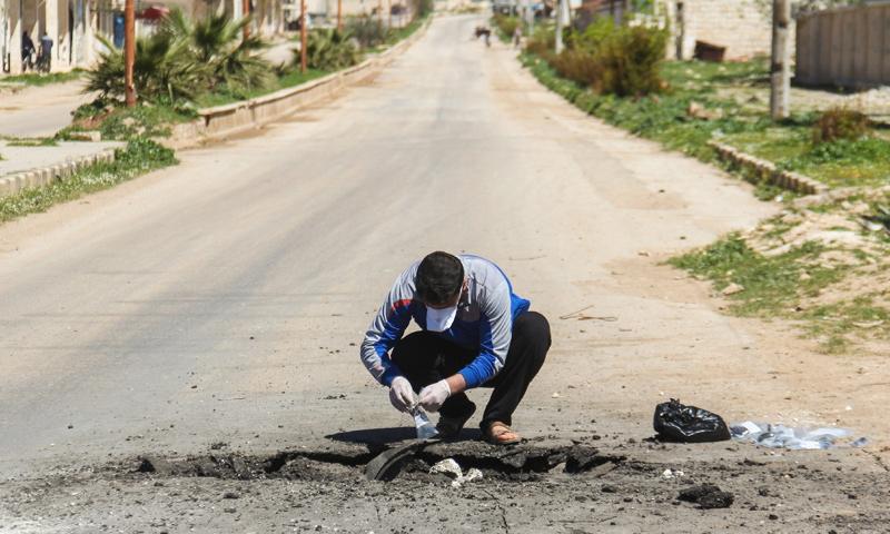 رجل سوري يجمع عينات من موقع الاستهداف الكيماوي في خان شيخون بريف إدلب- 7 نيشان-(AFP)