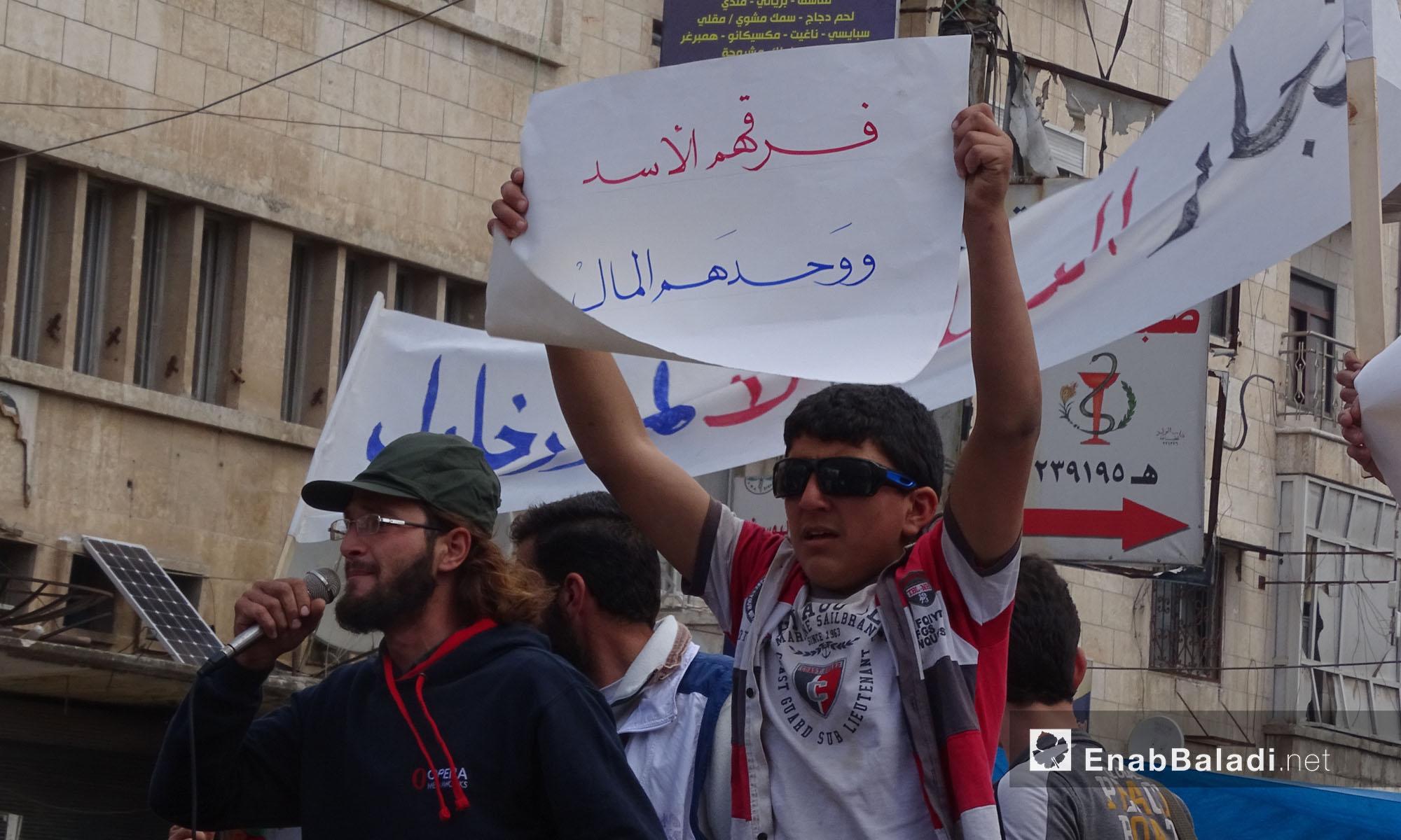 """طفل يحمل لافتة تُندد باتفاق """"المدن الخمس"""" في إدلب - 23 نيسان 2017 (عنب بلدي)"""
