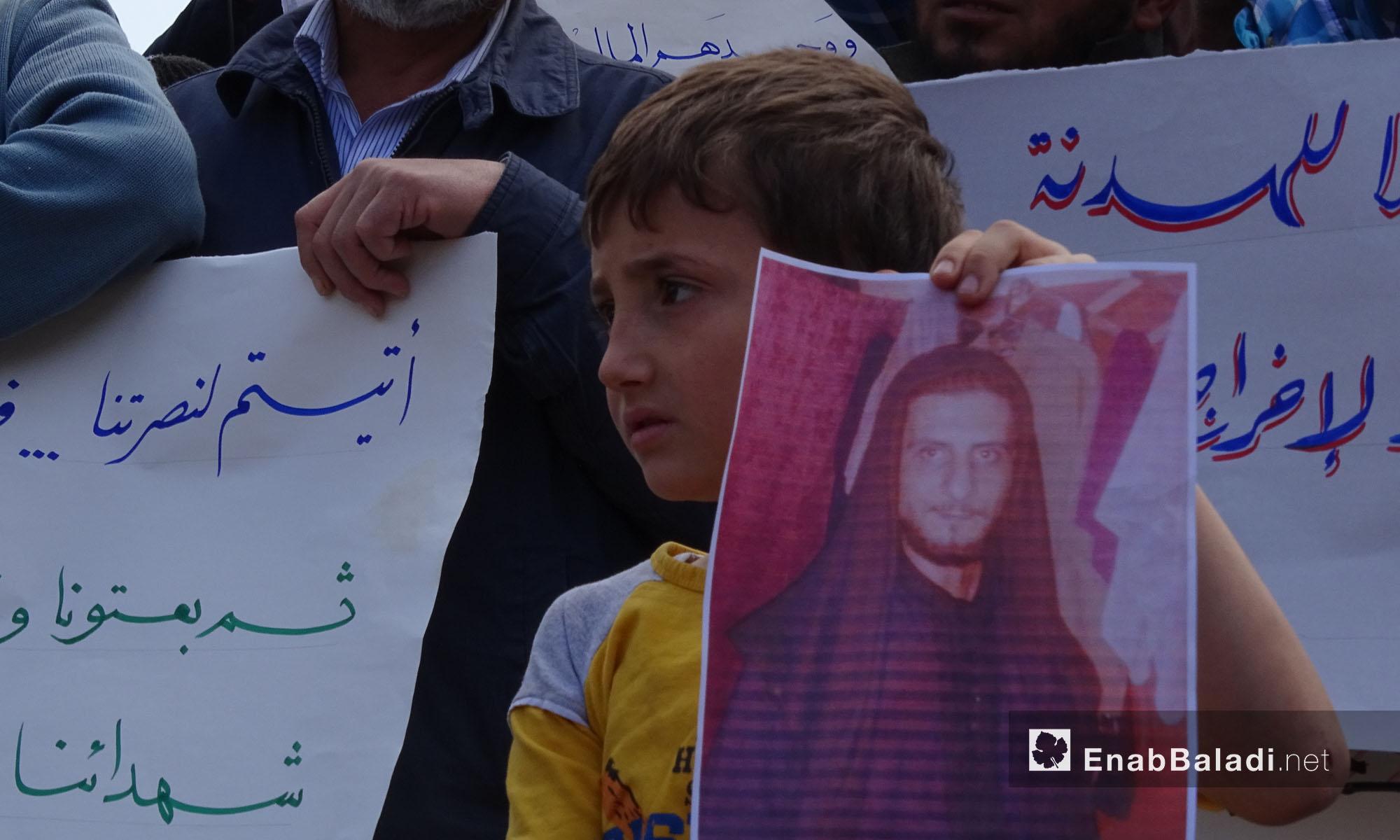 طفل يحمل صورة لأحد أقاربه مطالبًا بالمعتقلين خلال مظاهرة في إدلب - 23 نيسان 2014 (عنب بلدي)