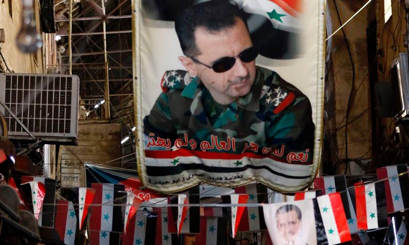 صورة رئيس النظام السوري بشار الأسد في إحدى الشوارع بدمشق- (AFP)