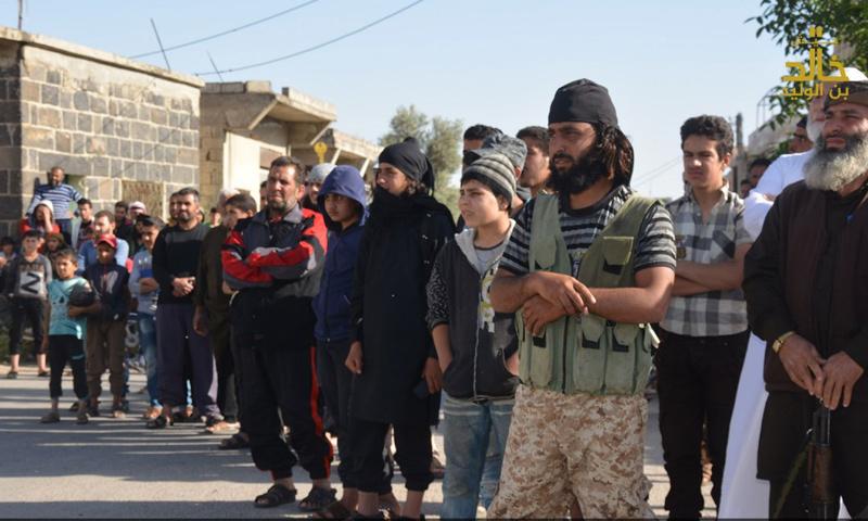 """أهالي تسيل في ريف درعا الغربي يتجمهرون أمام مقاتلين لـ """"جيش خالد"""" يقطعون رأس رجل بتهمة السحر- الأحد 30 نيسان 2017 (تلغرام)"""