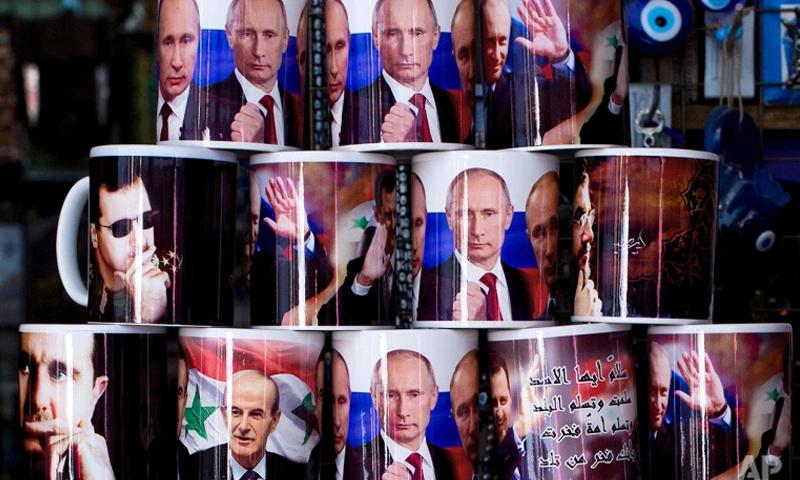 أكواب رسم عليها بشار الأسد ونظيره فلادييمير بوتين في إحدى أسواق دمشق-(AFP)