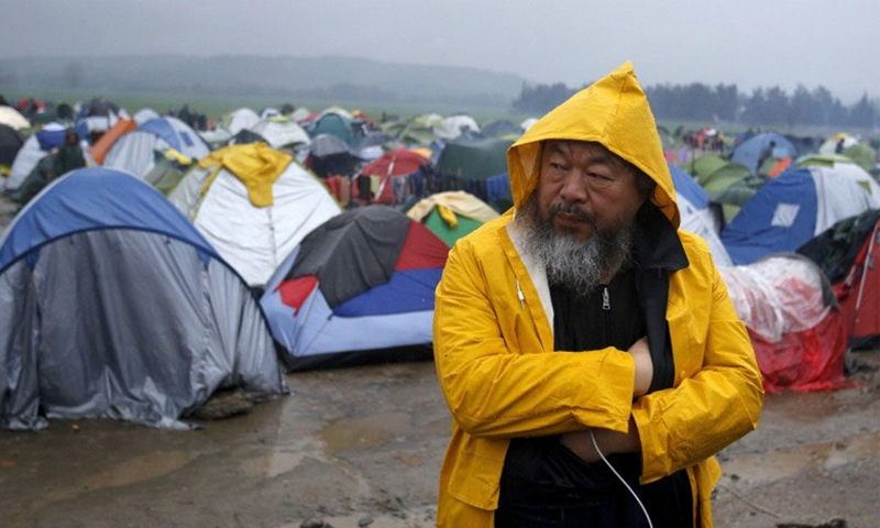 """الفنان الصيني آي وي وي خلال زيارته لمخيم """"إيدوميني"""" في اليونان - (انترنت)"""