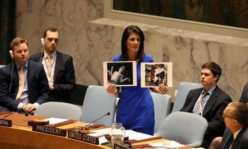 السفيرة الأمريكية لدى الأمم المتحدة، نيكي هيلي تحمل صور ضحايا مجزرة خان شيخون - نيسان 2017 (وكالات)