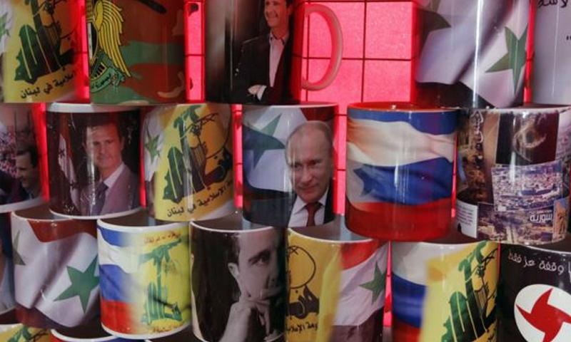 أكواب تحمل صور الرئيسان بشار الأسد وفلاديمير بوتين في إحدى محال مدينة دمشق - (AFP)