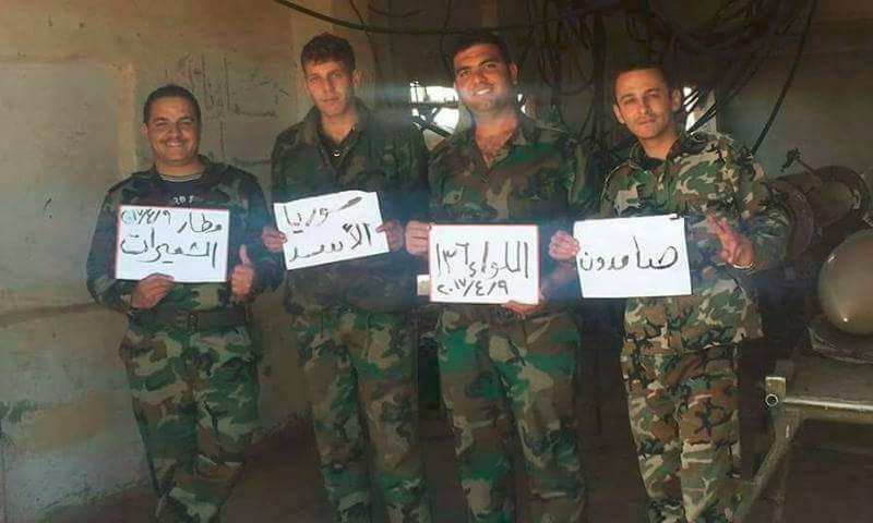 عناصر من قوات الأسد يرفعون لافتات داخل مطار الشعيرات شرق حمص - 9 نيسان 2017 (صفحات موالية للأسد في فيس بوك)