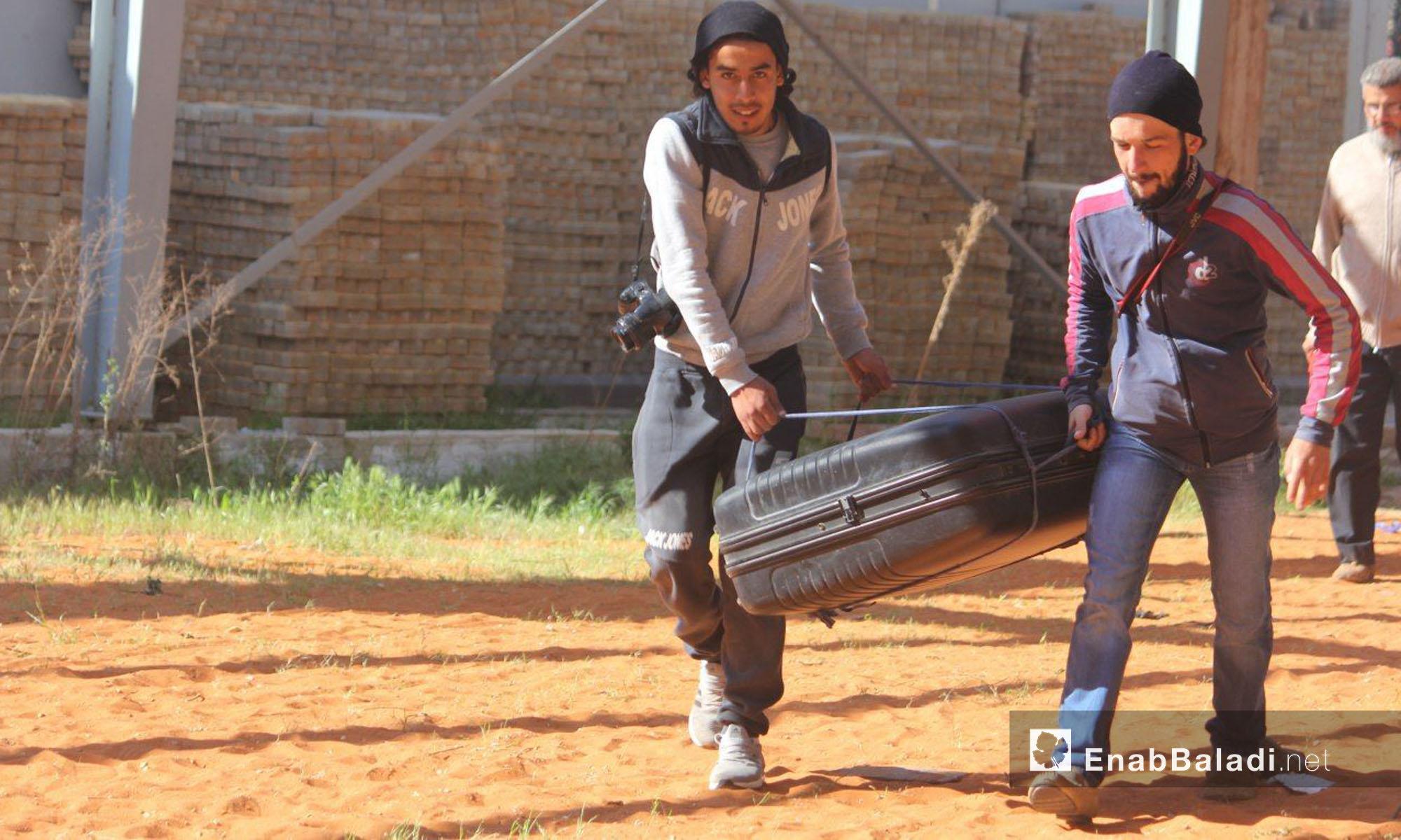 شابان يحملان حقيبة إلى الحافلة المتجهة إلى جرابلس - 24 نيسان 2017 (عنب بلدي)