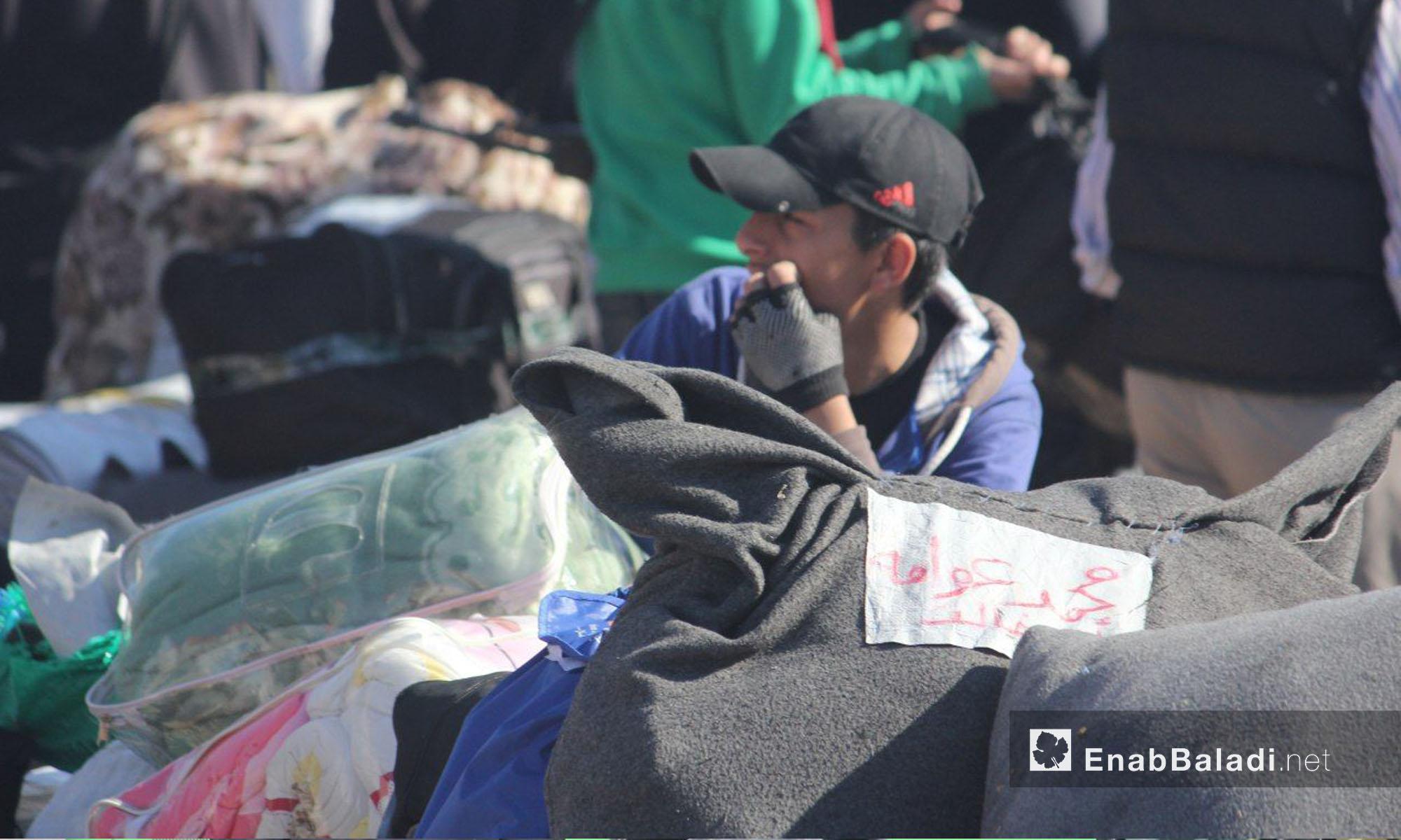شاب من حي الوعر  ينتظر قرب أمتعته تحضيرًا  للخروج إلى جرابلس - 24 نيسان 2017 (عنب بلدي)