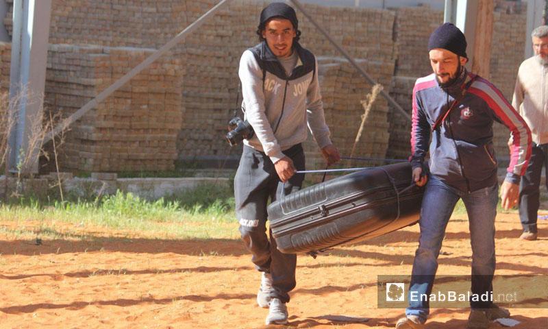 شابان يحملان حقيبة تحضيرًا للخروج من حي الوعر في حمص - 24 نيسان 2017 (عنب بلدي)