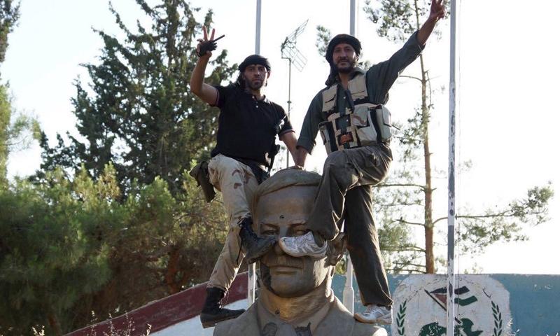 عناصر من الجيش الحر يضعون أقدامهم على تمثال حافظ الأسد في مدينة درعا - 21 حزيران 2015 - (رويترز)