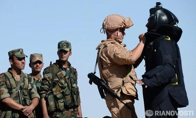 جندي روسي مع عناصر من قوات الأسد في محيط مدينة تدمر - (سبوتنيك)