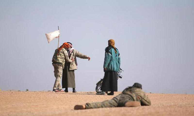 عنصر من قوات سوريا الديموقراطية يفتّش نازحين من مدينة الرقة- (رويترز)