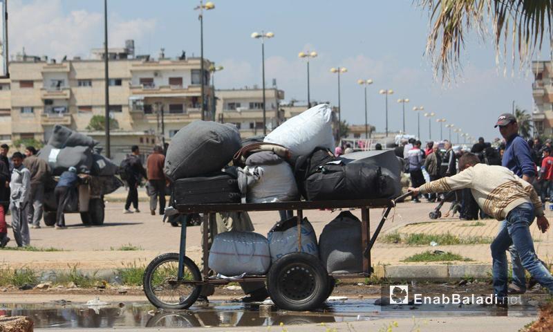 رجل يجر عربة حاملًا حقائبه قبل الخروج من حي الوعر في حمص - 17 نيسان 2017 (عنب بلدي)
