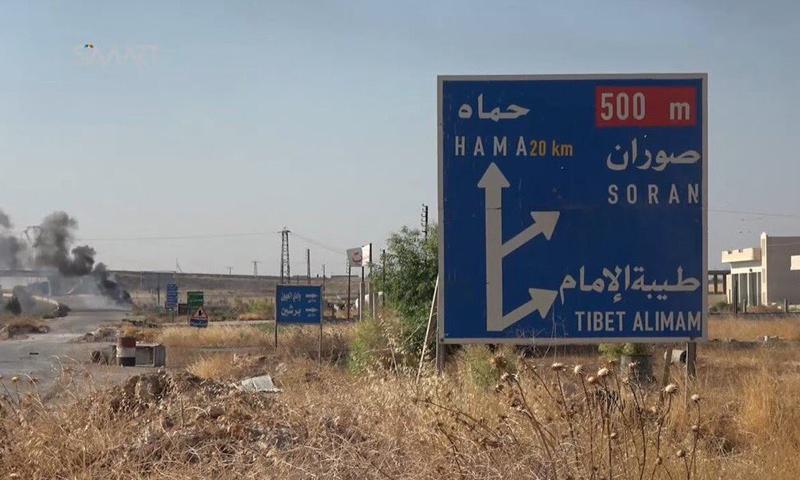 لافتة طرقية لموقع طيبة الإمام شمال حماة (إنترنت)