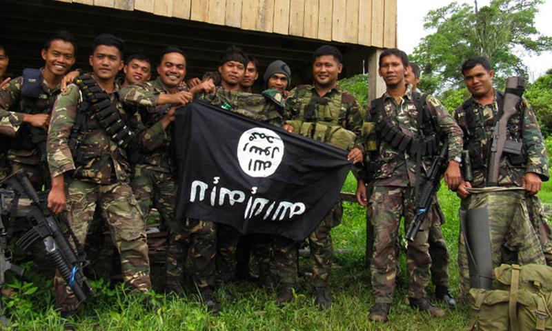 """جنود في الفيلبين يحملون راية وجدوها أثناء ملاحقة عناصر من تنظيم """"الدولة"""" (AFP)"""