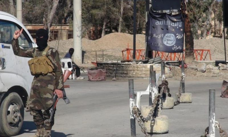 مقاتل من تنظيم الدولة الإسلامية على حاجز في مدينة الرقة - (انترنت)