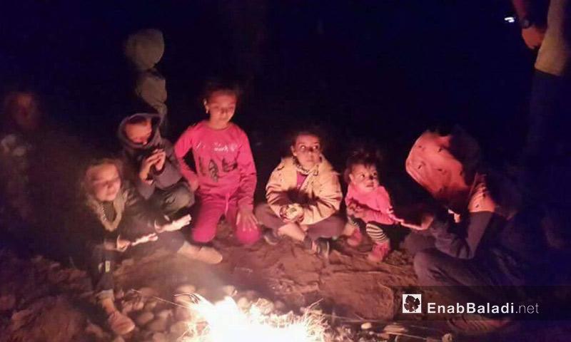 أطفال سوريون يتجمعون حول نار في ليل الصحراء بين المغرب والجزائر - أيار 2017 (عنب بلدي)