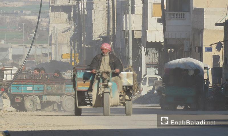 رجل مسن يستقل دراجة نارية بثلاثة عجلات في مدينة الباب بعد تحريرها - 19 آذار 2017 -(عنب بلدي)