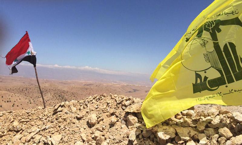 راية النظام السوري إلى جانب راية حزب الله اللبناني على جبال القلمون - (انترنت)