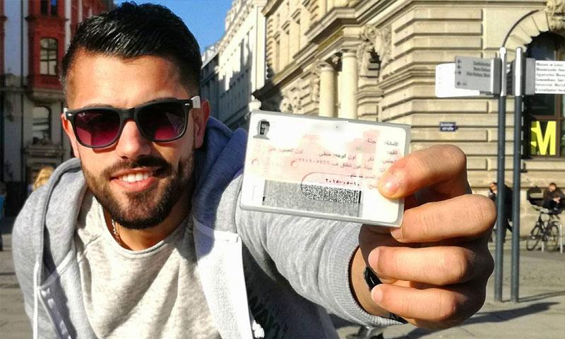 لاجئ سوري يحمل هويته في ألمانيا (إنترنت)